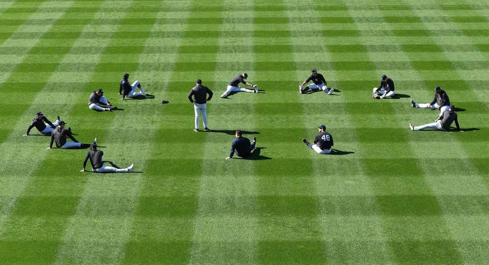 New York Yankees players stretch in the outfield