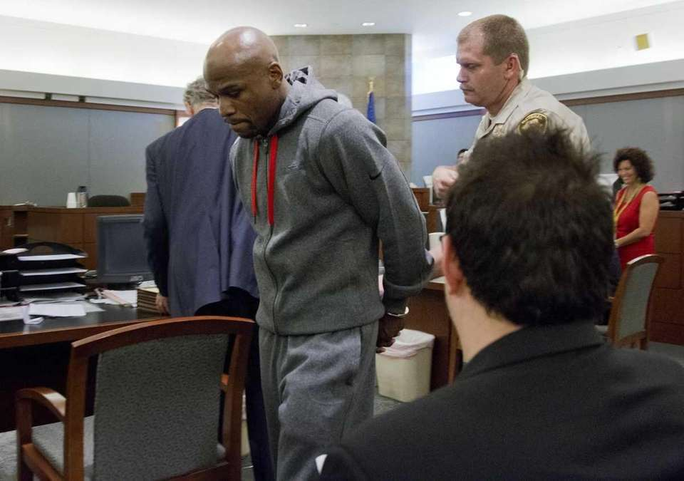 Floyd Mayweather Jr., left, is led away by