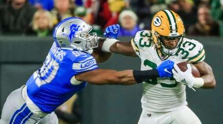 Lions defensive end Trey Flowers reaches to grab