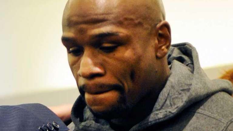 Boxer Floyd Maywether Jr. is led away in