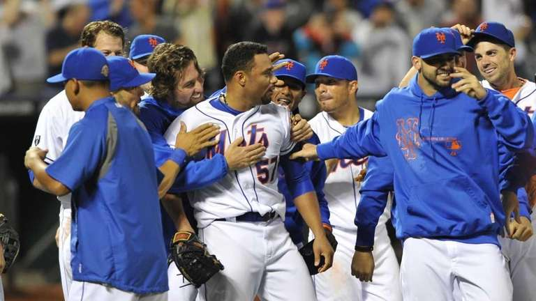 Johan Santana, center, is mobbed by teammates after