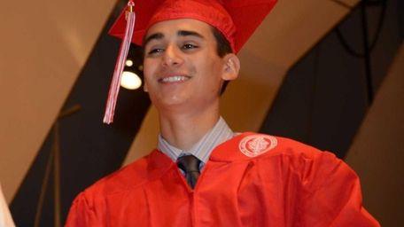 Justin Benigno, 17, of Massapequa, accepts his diploma
