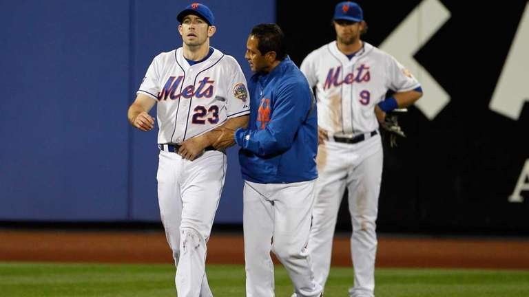 Head Trainer Ray Ramirez walks Mike Baxter #23