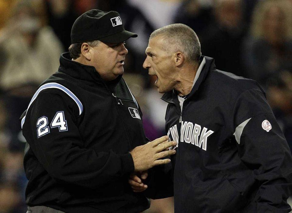 Umpire Jerry Layne (24) restrains Yankees manager Joe
