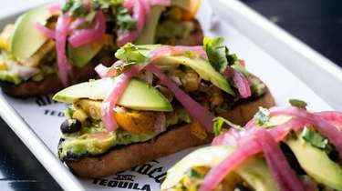 Avocado toast features grilled sourdough bread topped with