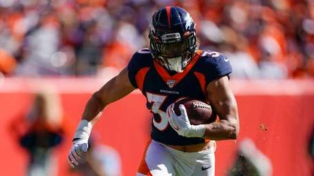 Broncos running back Phillip Lindsay runs with the