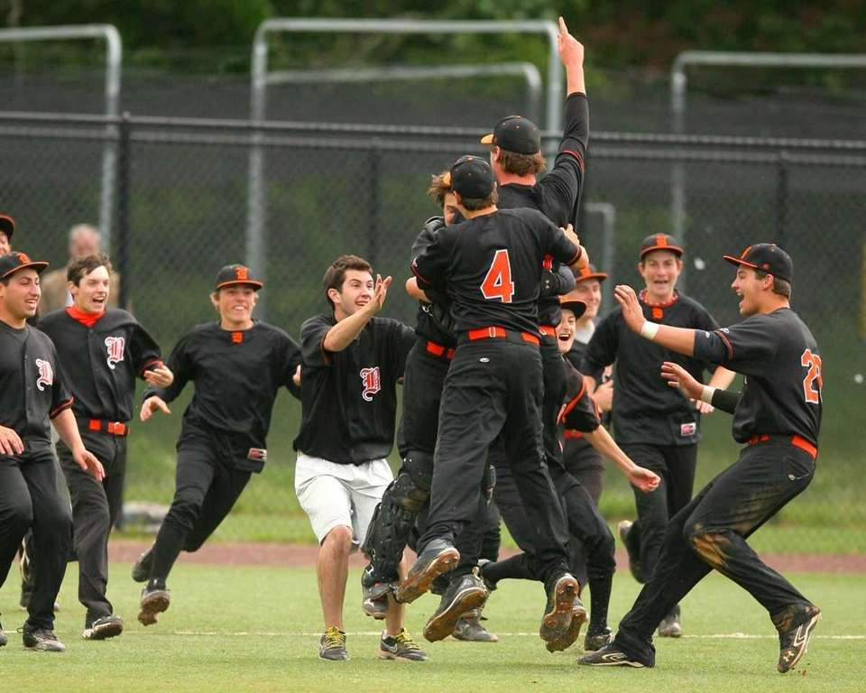 Babylon High School players rush the mound after