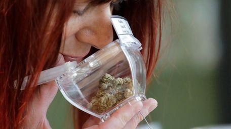 A customer sniffs a display sample of marijuana