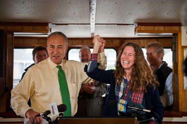 Sen. Charles Schumer raises the hand of Bonnie