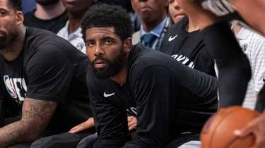 Nets guard Kyrie Irving, center, watches action against