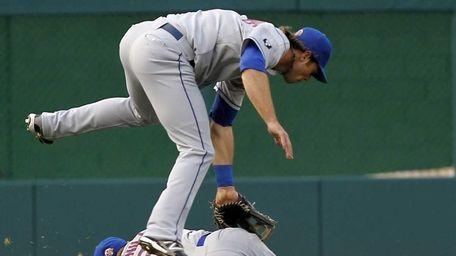Mets centerfielder Kirk Nieuwenhuis, top, goes over shortstop