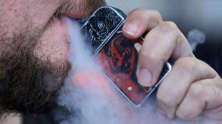 A man using an electronic cigarette exhales in
