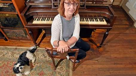Nesconset resident Jeannie Watson with the Spinet piano