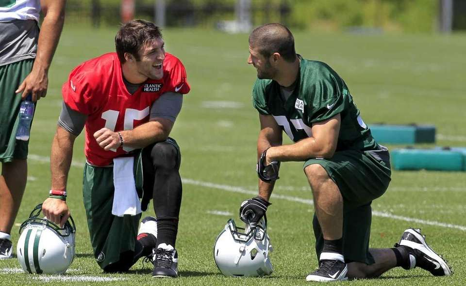 New York Jets quarterback Tim Tebow, left, talks