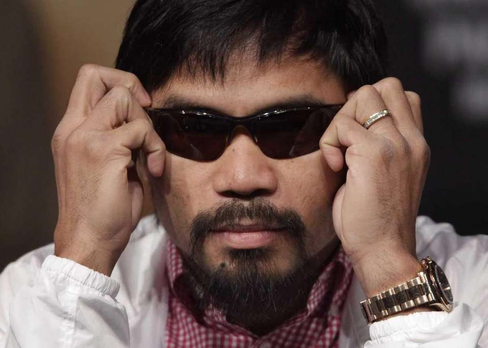 Manny Pacquiao puts on sunglasses during a press