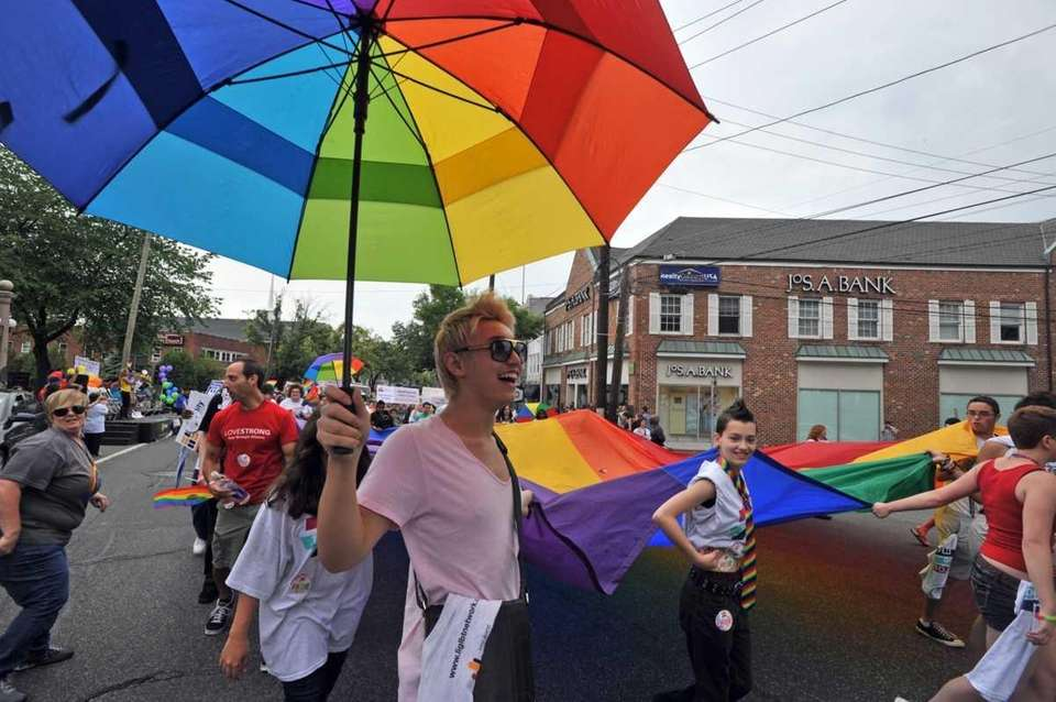 J.T., of Jericho, holds a rainbow-colored umbrella while