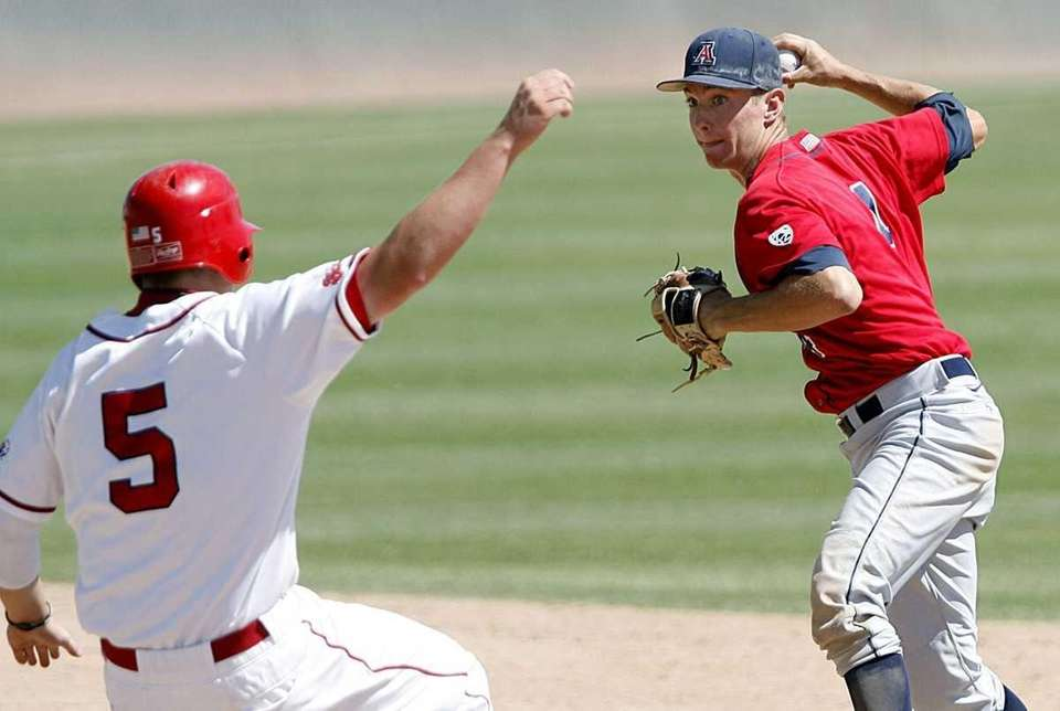 Arizona's Trent Gilbert, right, throws the ball to