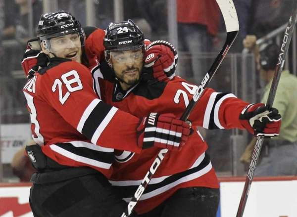 New Jersey Devils' Bryce Salvador, right, celebrates with