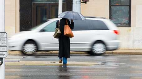A woman with an umbrella crosses Sunrise Highway