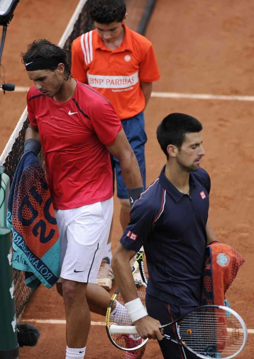 Spain's Rafael Nadal (L) passes by Serbia's Novak