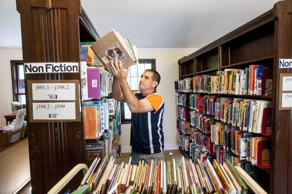 East Hampton Library Director Dennis Fabiszak moves books