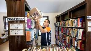 East Hampton Library Director Dennis Fabiszak moves books