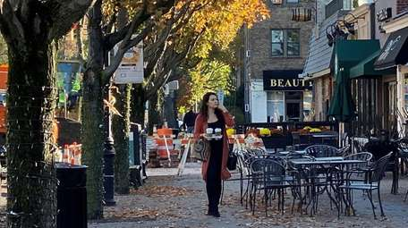 Pedestrians walk along Seventh Street in Garden City,