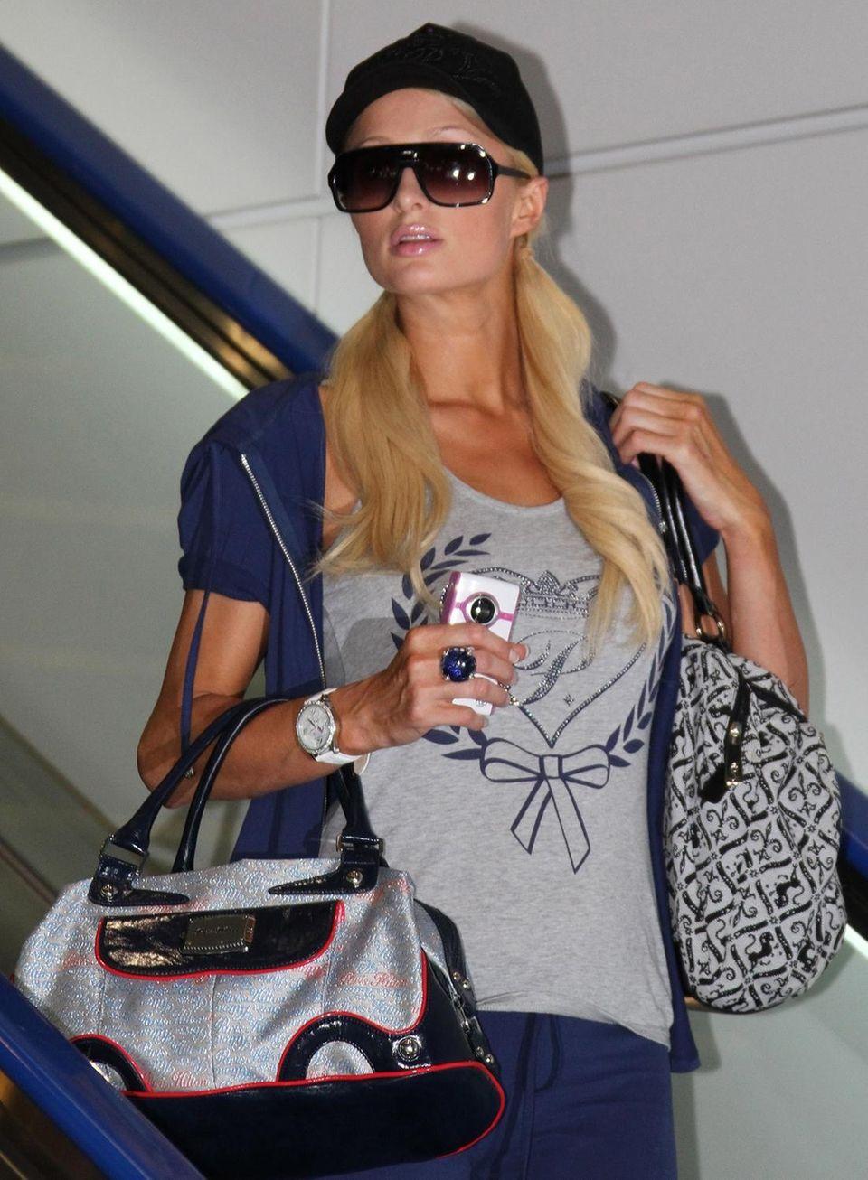 Socialite Paris Hilton arrives at a departure lounge