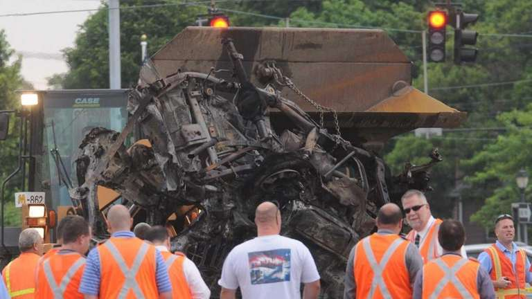 A bulldozer removes a mangled SUV from the
