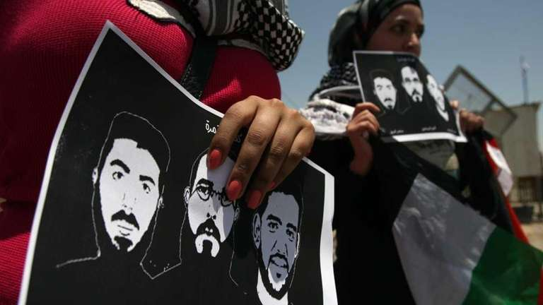 Female Palestinian protestors hold pictures of jailed Palestinian