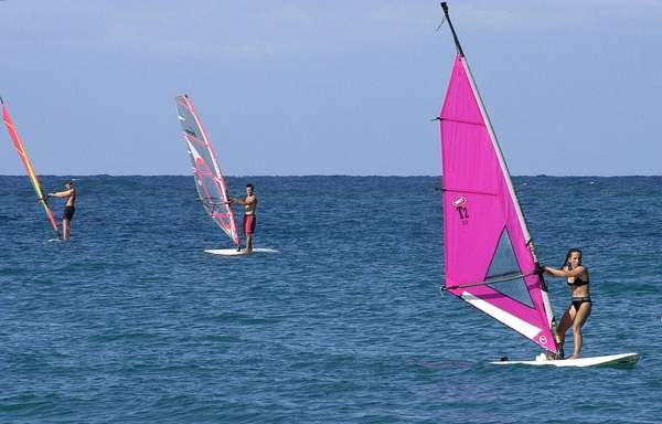 Windsurfers ride their boards at Cabarete Beach, about