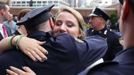 Caitlyn Figoski is hugged by members of the