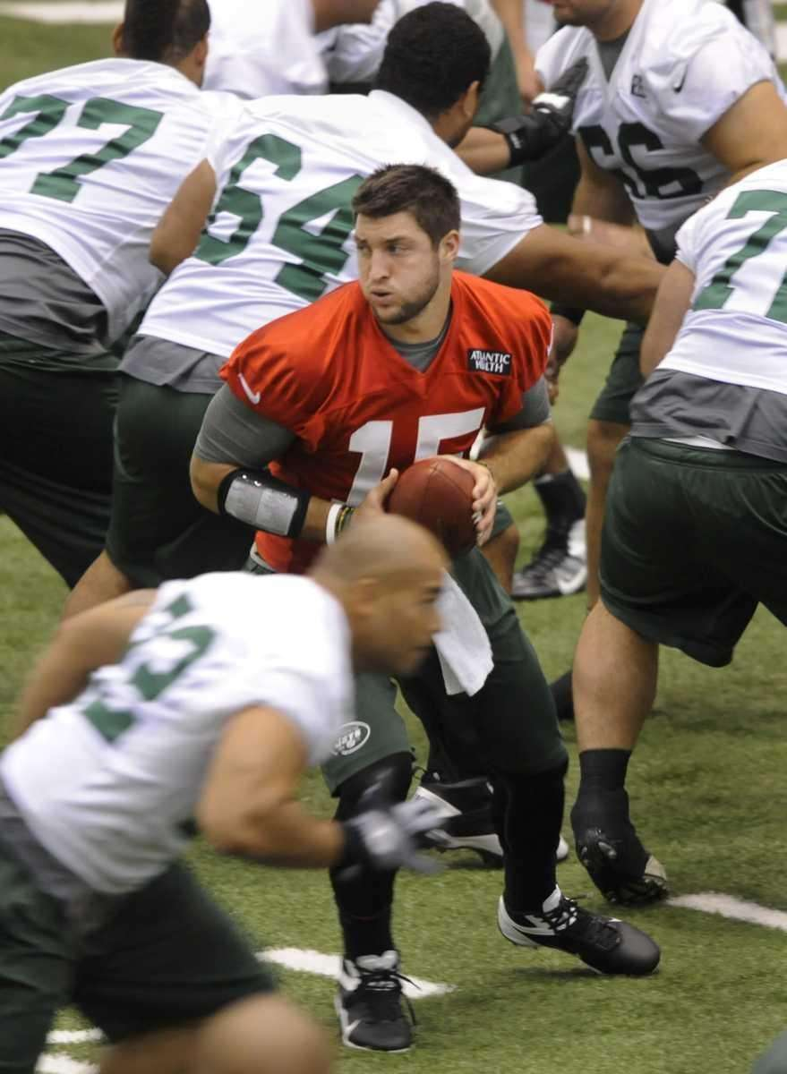 Jets quarterback Tim Tebow looks to hand off