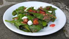 Spinach coated with a warm strawberry-rhubarb dressing will