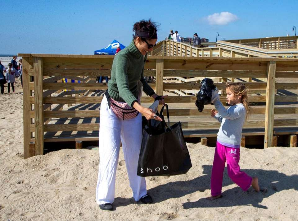 Phoebe Tzimas, right, helps clean up the beach