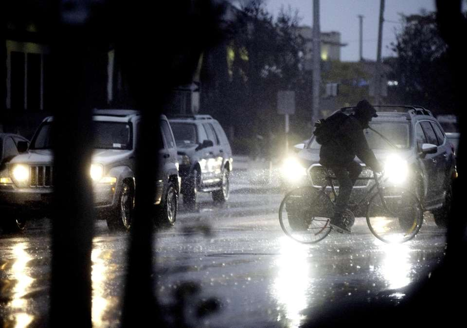 A man rides his bike in the rain