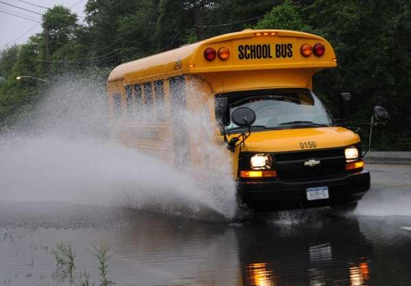 A school bus splashes through a large puddle