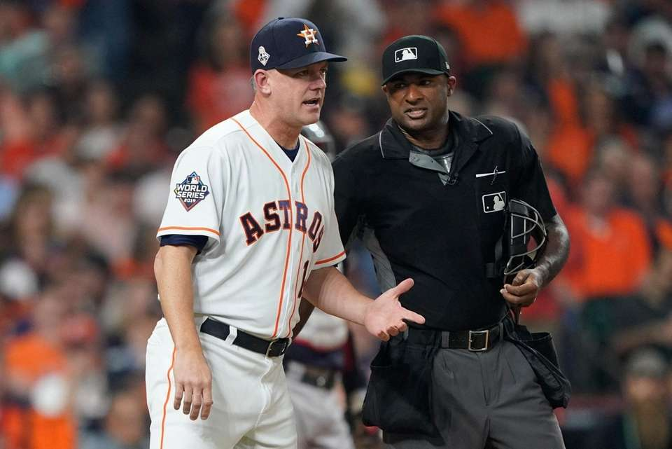 Houston Astros manager AJ Hinch argues a call