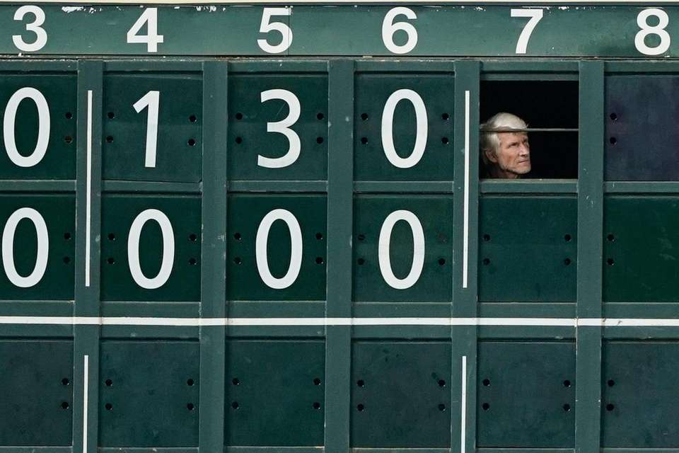 A worker watches from the outfield scoreboard during