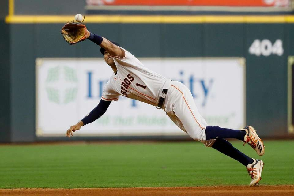Houston Astros shortstop Carlos Correa catches a line
