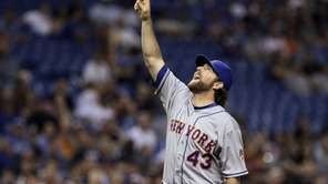 Mets starting pitcher R.A. Dickey points to the