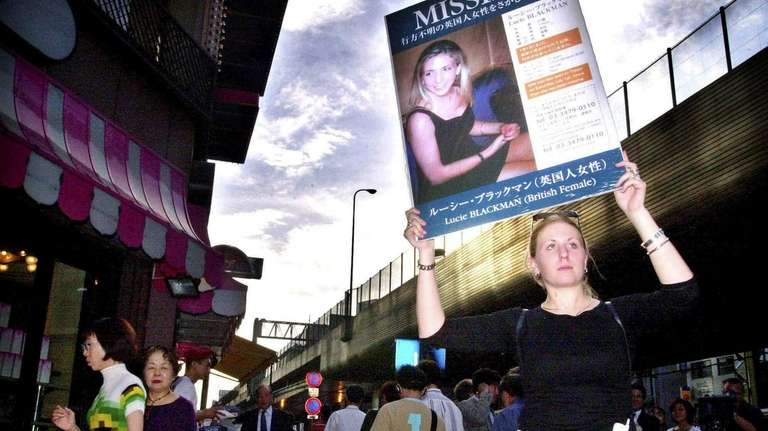 Holding a poster with Lucie Blackman's picture, Sophie