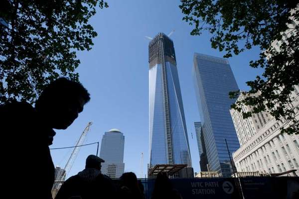 Pedestrians walk past One World Trade Center in