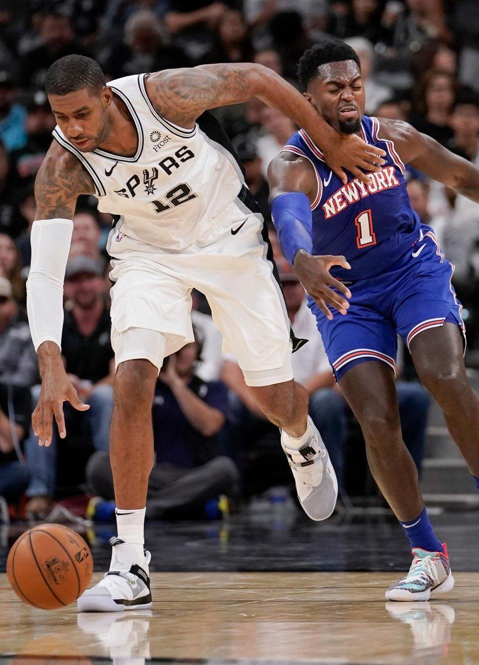 The San Antonio Spurs' LaMarcus Aldridge tangles with