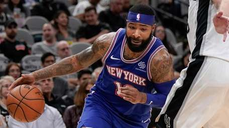 The Knicks' Marcus Morris, left, drives against the