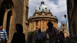 People pass the Radcliffe Camera, an 18th century