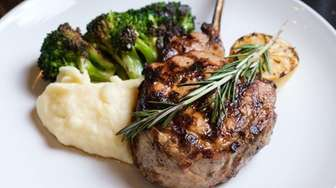 A tomahawk-style grilled veal rib chop with mashed