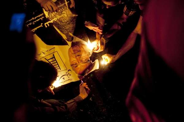 Egyptian demonstrators set fire to campaign sign of