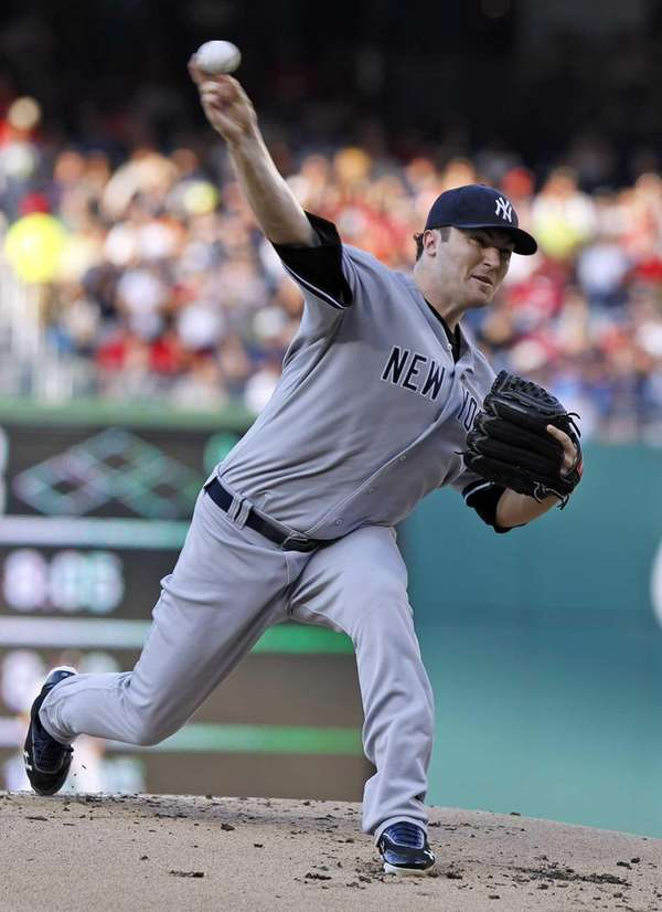 Yankees starting pitcher Phil Hughes throws during the