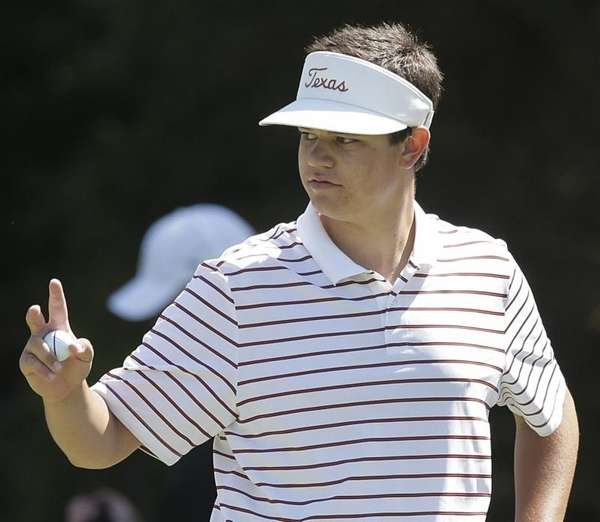 Amateur Beau Hossler waves after making a birdie